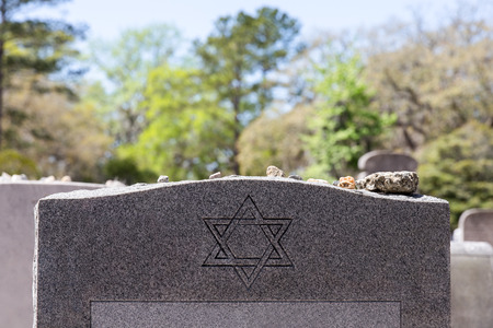 Headstone in a Jewish cemetery with Star of David and memory stones.  Selective focus on the foreground.