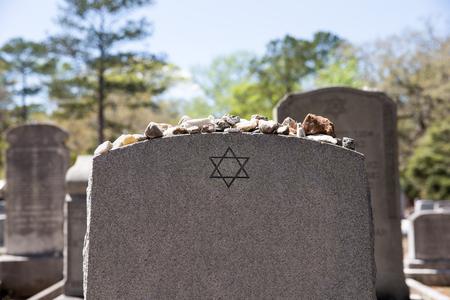 Hoofdsteen in een joodse begraafplaats met de ster van david en geheugenstenen. Selectieve focus op de voorgrond. Kopieer de ruimte.
