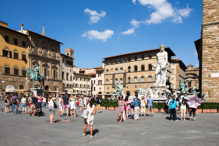 FLORENCE, ITALY - July 28, 2015:  Piazza della Signoria, or Signoria Square, in Florence, Italy taken during the summer and showing tourists, the Fountain of Neptune, and other historic statues and buildings.  The square is a focal point of the city and a Editorial