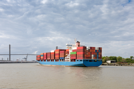 Fully loaded cargo container ship approaching the Talmadge Memorial Bridge as it enters Port of Savannah in Georgia.  Copy space in sky if needed. Stock Photo