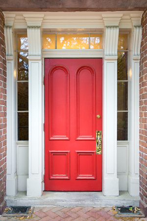 Red door framed by white columns, side windows, and set in red brick.  Classic look with warm lighting.
