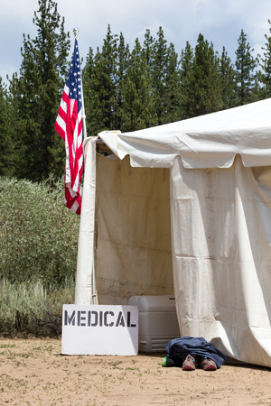Medical tent entrance with a hand-made medical sign and an American Flag.  Runners aid station, as indicated by the shoes outside of the entrance.