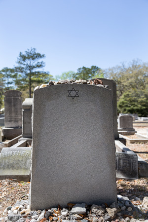 Headstone in a Jewish cemetery with Star of David and memory stones.  Selective focus on the foreground.  Copy space. Stock Photo