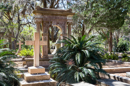 Historic Bonaventure Cemetery in Savannah, GA.  Serene scene with prominent cross in the foreground, lush vegetation, and Spanish moss. Stock Photo