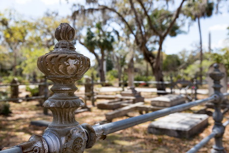 Historic Bonaventure Cemetery in Savannah, GA.  Old rusty wrought iron post and fence.  Selective focus on foreground to accommodate copy if needed. Stock Photo
