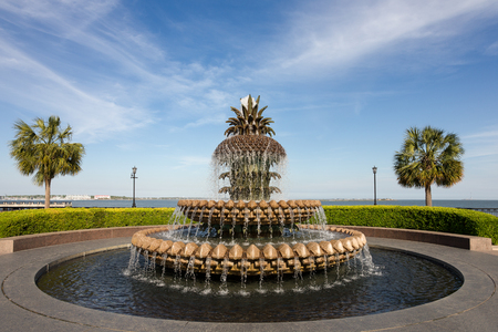 Pineapple water fountain in Waterfront Park in Charleston, SC.  Pineapples are a symbol of hospitality in the American South.  Copy space in sky if needed. Stock Photo