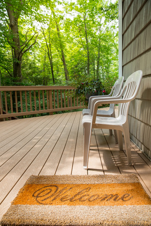 Welcome mat leading to a pair of chairs on an outdoor deck.  Relaxing and welcoming outdoor scene.  Vertical orientation.