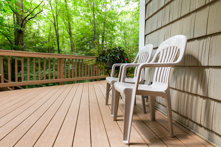 Two chairs on an outdoor deck in the woods.  Relaxing and welcoming outdoor scene. Stock Photo
