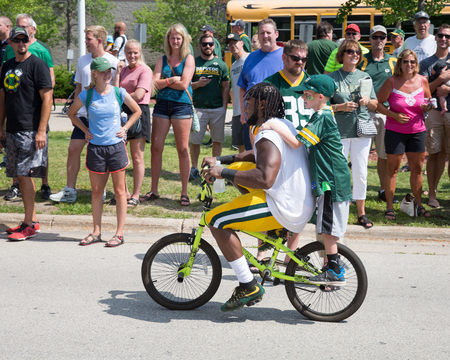 Green Bay, WI - August 1, 2017:  Aaron Jones rides a young fans bike after football practice.  The community owned Green Bay Packers have a long tradition of player involvement with fans.