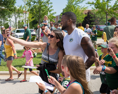 Green Bay, WI - August 1, 2017:  Green Bay Packer DeAngelo Yancey takes selfie with a fan after football practice.  The community owned team has a long tradition of player involvement with fans. Editorial