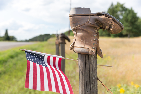 Boot on a barbed wire fence post with an American flag.  Concepts could include rural culture, patriotism, other. Stock Photo