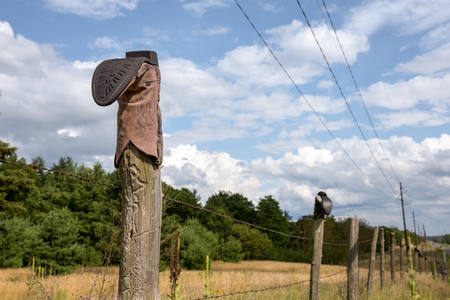 Cowboy boot on a barbed wire fence post with dramatic sky.  Concepts could include rural culture, traditions, western life, humor, others.