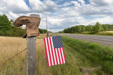 Boot on a barbed wire fence post with an American flag and dramatic sky.  Concepts could include rural culture, patriotism, other.