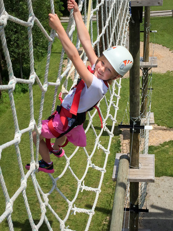 Daring young girl climbing on an elevated rope net on an obstacle course expressing joy, courage, and determination.