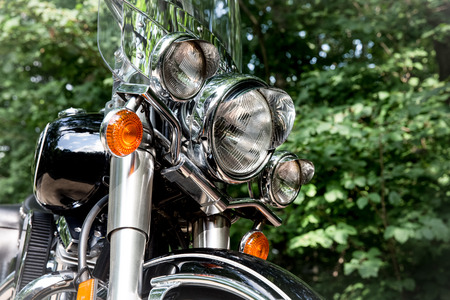 Retro motorcycle headlight close up.  Concepts could include adventure, travel, nostalgia, transportation, others. Stock Photo
