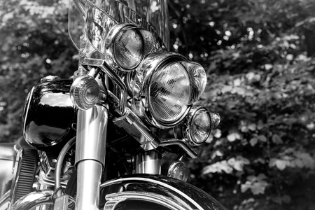 Retro motorcycle headlight close up.  Photographed in black and white for a vintage look.  Concepts could include adventure, travel, nostalgia, transportation, others.