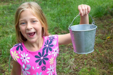 Smiling girl holding an empty tin pail or bucket.  Grinning and looking at camera.  Room for copy on the pail if needed.