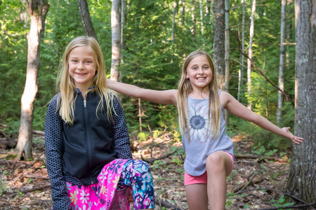 Two happy girls in the forest, looking at the camera with confident, happy expressions.