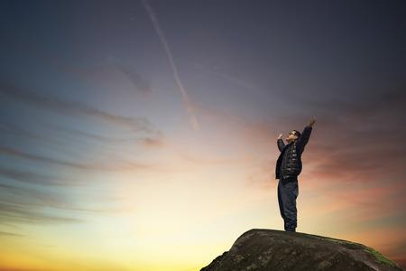 alabanza: hombre con las manos levantadas en el concepto de la puesta del sol para la religión, el culto, la oración y la alabanza