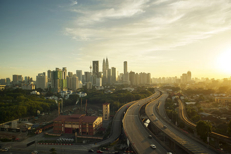 highway night: Dramatic scenery of elevated highway heading towards Kuala Lumpur city centre during sunset. Stock Photo