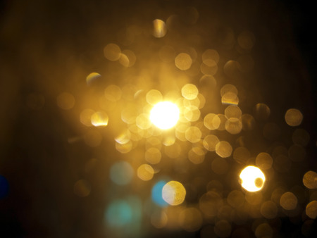 gold colour: abstract black background, gold bubble lights or snowflakes falling at night. Bokeh Christmas background with circle designs or blurred stars shining, glitter magic background