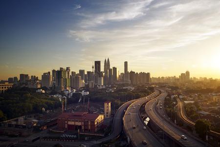 highway night: Dramatic scenery of elevated highway heading towards Kuala Lumpur city centre during sunset. Stock Photo