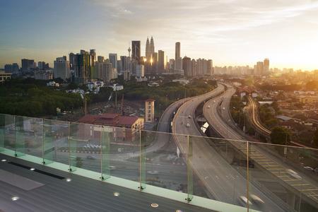 Dramatisch landschap van verhoogde snelweg richting centrum van Kuala Lumpur tijdens zonsondergang.