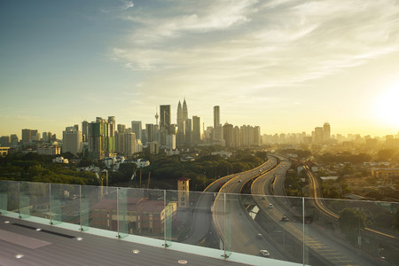 Dramatic scenery of elevated highway heading towards Kuala Lumpur city centre during sunset. 免版税图像