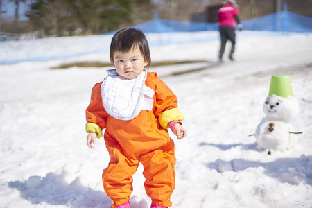 pampers: Karuizawa,Japan - 30,March,2015 : Adorable baby play with snow  . Karuizawa is one of the few ski resorts in Japan. Conveniently located just minutes from the bullet train station and ski area, Karuizawa Prince Hotel pampers you with deluxe service and am Editorial