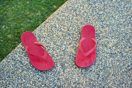 pair of red comfortable slipper placed of stony floor Stock Photo
