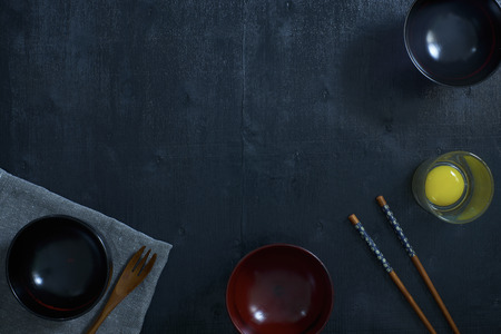table linen: Black color wooden table top view. On the table are the Japanese wooden spoon, chopsticks, bowl,fresh raw eggs and table linen. Stock Photo