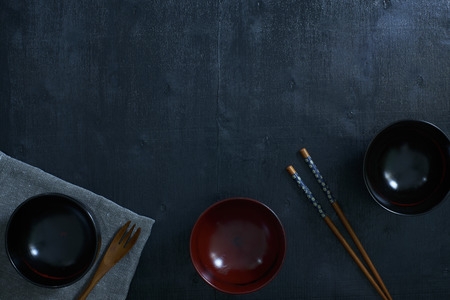 japanese background: Black color wooden table top view. On the table are the Japanese wooden spoon, chopsticks, bowl and table linen.