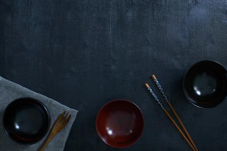 comida japonesa: de color negro mesa de madera vista desde arriba. Sobre la mesa hay la cuchara de madera, palillos, taza y de mesa japonés.