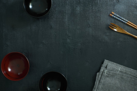 table linen: Black color wooden table top view. On the table are the Japanese wooden spoon, chopsticks, bowl and table linen.