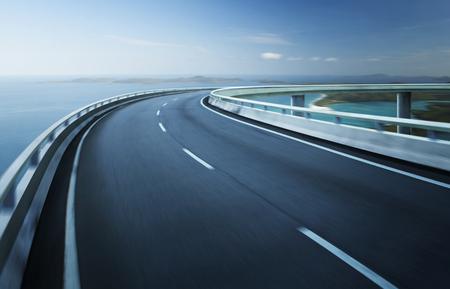 route: Autoroute viaduc flou de mouvement avec la Côte d'horizon de fond. Banque d'images