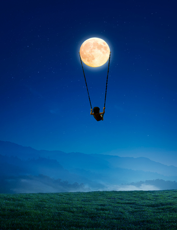 green little planet earth: Little girl on a swing in the form of the moon Stock Photo