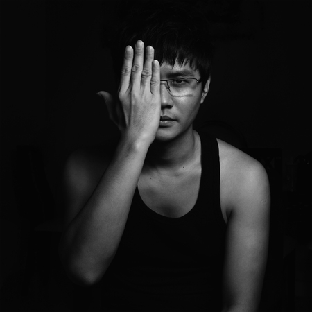 one eye: young Asian man covering his face with a palm. Black and White