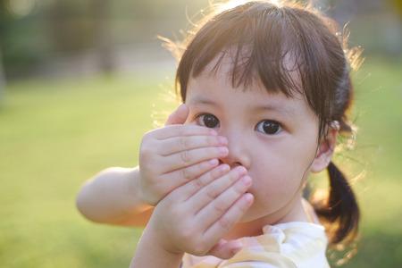 petite fille triste: fille timide couvrant son visage Banque d'images