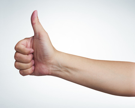 mans hand showing close up of the thumbs up sign on white background