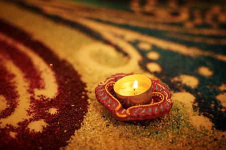 rangoli: Traditional diya lamp lit on colorful rangoli Stock Photo