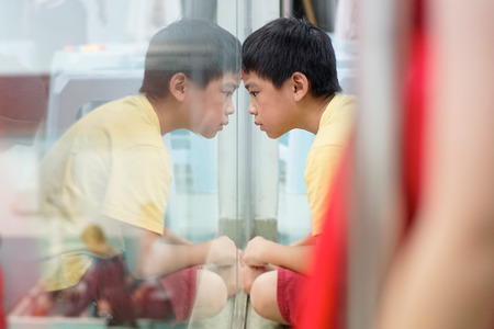 Sad upset waiting boring depressed child (boy) near a window, reflection. Stock Photo