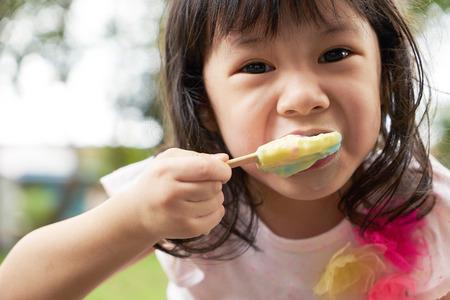 Recht kleines Mädchen ein Eis essen im Freien