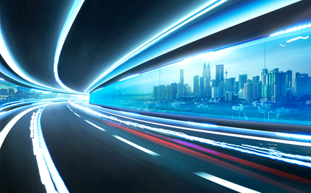 express lane: Abstract blurred speed motion road in glass tunnel over the city,with light trail Stock Photo