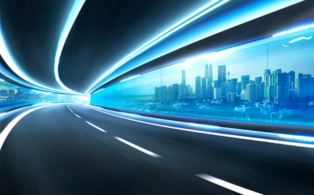Abstract blurred speed motion road in glass tunnel over the city Imagens
