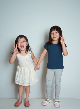standing together: Two little happy asian sisters on plain background