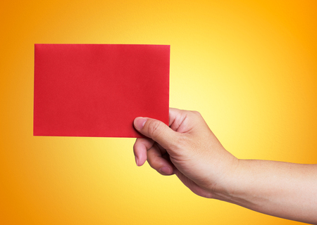 red hand: Red envelope in the hand isolated on orange background Stock Photo