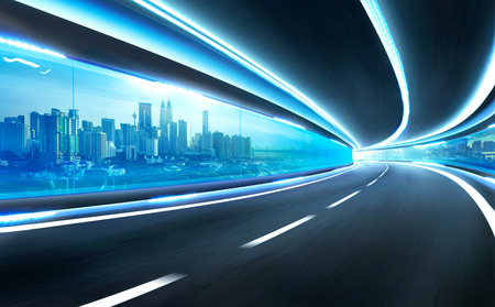 express lane: Abstract blurred speed motion road in glass tunnel over the city Stock Photo
