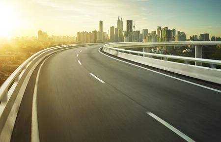 curvas: Carretera del movimiento paso elevado de la falta de definición con el fondo de la ciudad. Foto de archivo