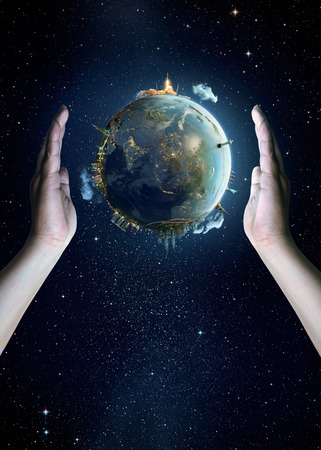 triangulum: Saving Earth concept, Hands holding Earth with a sky and space background.