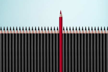 dissent: Red pencil standing out from crowd of plenty identical black fellows on white table. Leadership, uniqueness, independence, initiative, strategy, dissent, think different, business success concept Stock Photo